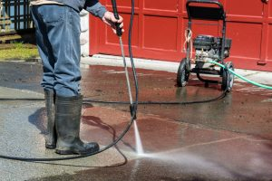 bigstock-Man-Cleaning-Driveway-with-Pre-46778653